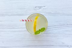 Lemonade drink in a glass with fresh lemon and mint over white wooden background, top view. From above, overhead royalty free stock image