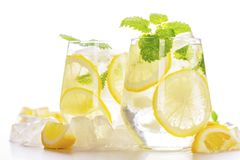 Lemonade drink in a glass. Water, ice, lemon slice and mint on white background Stock Photography