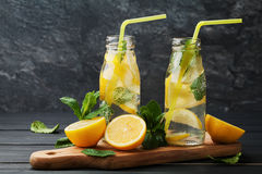 Lemonade drink of soda water, lemon and mint in jar on black background. Lemonade drink of soda water, lemon and mint leaves in jar on black background Stock Images