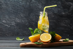 Lemonade drink of soda water, lemon and mint in jar on black background Royalty Free Stock Images