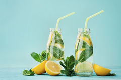 Lemonade drink of soda water, lemon and mint in jar on turquoise background Royalty Free Stock Photo