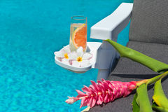 Lemonade with flowers at swimming pool. A glass of fresh lemonade, frangipani flowers and torch Ginger flower on resting chair, by swimming pool Royalty Free Stock Image