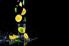 Lemonade with flying lemon and mint, isolated on a black background, free space. Cold summer lemonade, photo for advertising stock photo