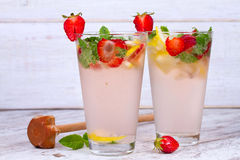 Lemonade with fresh strawberries, mint and lemon on wooden background. Stock Photos
