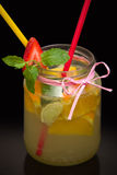 Lemonade with fruits and straws Stock Images