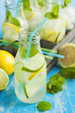 Lemonade in glass bottle with ice and mint Stock Photo