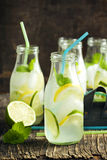 Lemonade in glass bottle with ice and mint Stock Image