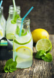 Lemonade in glass bottle with ice and mint Stock Photos