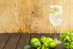 Lemonade in glass and green lemon on wooden background.Drink for health. Close up Royalty Free Stock Image