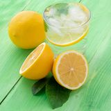 Lemonade in a glass, a lemon half, fresh leaves on the green tab Royalty Free Stock Images