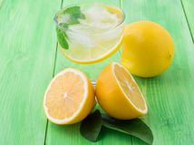 Lemonade in a glass, a lemon half, fresh leaves on the green tab Royalty Free Stock Photo