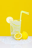 Lemonade in glass yellow background Stock Photo