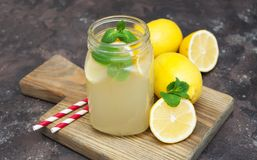 Lemonade. Homemade lemonade with fresh lemon and mint on a stone background Stock Images