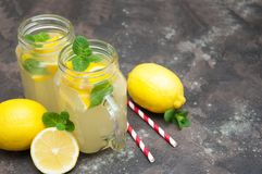 Lemonade. Homemade lemonade with fresh lemon and mint on a stone background royalty free stock photography