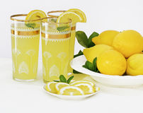 Lemonade. Ice-cold drinks of  lemonade with mint in glasses with gold trim and a dish of freshly picked  lemons to the side with lemon leaves,  slice lemons at Stock Photos