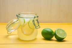 Lemonade with ice, lemon and lime in a jar on a yellow wooden ba. Ckground. Summer drink Royalty Free Stock Photo