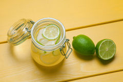 Lemonade with ice, lemon and lime in a jar on a yellow wooden ba. Ckground. Summer drink Stock Photo