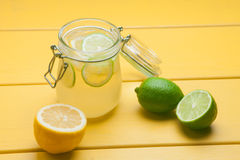 Lemonade with ice, lemon and lime in a jar on a yellow wooden ba. Ckground. Summer drink Stock Photos