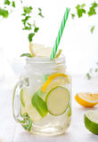 Lemonade with ice, lemon and lime slices in jar, straw. Royalty Free Stock Images
