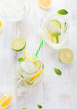 Lemonade with ice, lemon and lime slices in jar, straw. Royalty Free Stock Photos