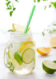 Lemonade with ice, lemon and lime slices in jar, straw. Lemonade with ice, lemon and lime slices in a jar with straw in a white summer wooden background royalty free stock photo