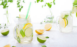 Lemonade with ice, lemon and lime slices in a jar with straw. In a white summer wooden background royalty free stock image