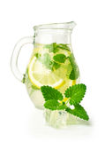 Lemonade with ice and mint in a glass jug. Isolated on white Royalty Free Stock Image