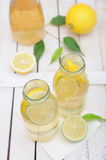 Lemonade in the jug and glasses with lemons and lime on  rustic table Stock Photography