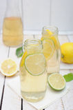 Lemonade in the jug and glasses with lemons and lime on rustic table Stock Photos