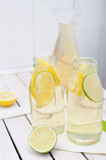 Lemonade in the jug and glasses with lemons and lime on white table Royalty Free Stock Photography