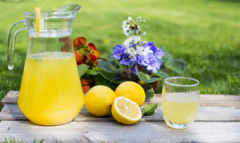 Lemonade in the jug and lemons on the table Royalty Free Stock Images
