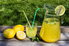 Lemonade in the jug and lemons on the table Stock Photos