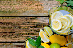 Lemonade in the jug with mint and lemon on the table. Royalty Free Stock Photos