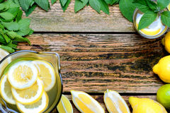 Lemonade in the jug with mint and lemon on the table. Stock Image
