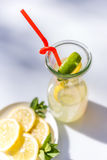 Lemonade in the jug with red straw and lemons on the table outdoor. Royalty Free Stock Image