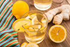 Lemonade with lemon and ginger in a transparent glass on a wooden table Stock Photo