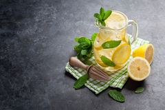 Lemonade with lemon, mint and ice. On stone table. View with copy space royalty free stock image