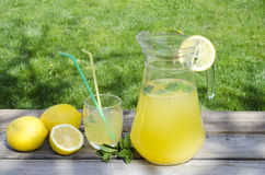 Lemonade and lemon on wood. Isolated on green grass background Royalty Free Stock Photos
