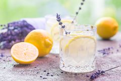 Lemonade with lemons and lavender. On stone table over nature background stock photos