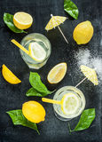 Lemonade, lemons, leaves on black chalkboard Royalty Free Stock Photography
