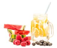 Lemonade in a mason jar with a drinking straw decorated with slices of watermelon,raspberries and blueberries  on white ba. Lemonade in a mason jar with a Royalty Free Stock Images