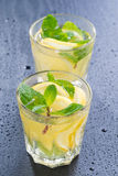 Lemonade with mint in glasses on a dark background, vertical Stock Images