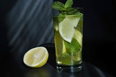 Lemonade or mojito cocktail with lemon and mint, cold refreshing drink or beverage with ice royalty free stock photography
