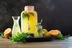 Lemonade with orange, lemon and mint in mason jar. Summer detox drink. Lemonade with orange, lemon and mint in different mason jar on black and wooden board stock photo