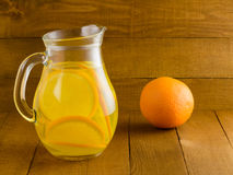Lemonade from oranges in a glass pitcher and mugs on a wooden table. Royalty Free Stock Photos