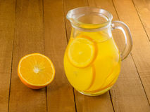 Lemonade from oranges in a glass pitcher and mugs on a wooden table. Royalty Free Stock Photography