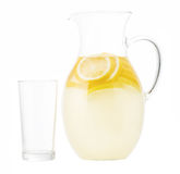 Lemonade pitcher with lemon slices and empty glass  isolated on Royalty Free Stock Photography