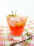 Lemonade with rhubarb and rosemary on napkin. Lemonade with rhubarb and rosemary in a glass on a checkered napkin on a wooden boards background Royalty Free Stock Photography