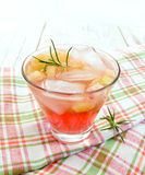 Lemonade with rhubarb and rosemary on napkin. Lemonade with rhubarb and rosemary in a glass on a pink checkered napkin on a wooden boards background Royalty Free Stock Images