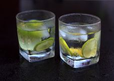 Lemonade served on a dark marble bar with a lime Royalty Free Stock Images